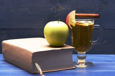 vin chaud: Un verre de délicieux glintwein ou vin chaud à la cannelle et de pomme verte fraîche naturelle avec un livre sur fond bleu vinage bois