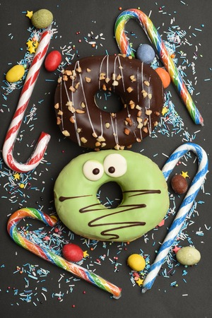 bonbons: Brown and green funny glazed donuts with chocolate, sprinkles and nuts, striped caramel candies, colorful dragee with raisins or peanuts inside on black background Stock Photo