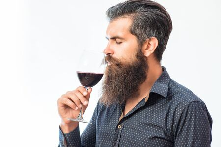 sniff: handsome bearded rich man with stylish hair mustache and long beard on serious face in blue fashion shirt holding glass and sniff smell of red wine isolated on white, copy space Stock Photo