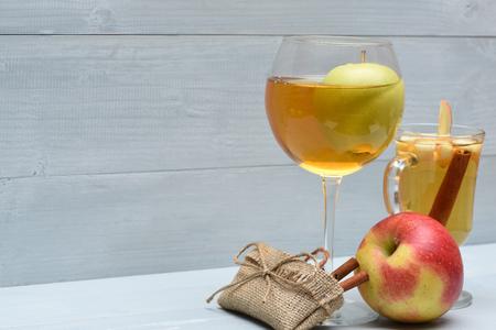 vin chaud: Verre de jus de pomme avec naturel pomme fraîche verte à l'intérieur et délicieux glintwein ou vin chaud, la cannelle et le sac de sac avec de la ficelle sur fond de bois cru Banque d'images