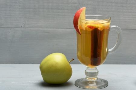 vin chaud: Un verre de délicieux glintwein ou vin chaud à la cannelle placé à l'intérieur et de pomme verte fraîche naturelle sur fond de bois vinage