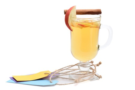 vin chaud: Glass of delicious glintwein or mulled hot wine with cinnamon, colorful tags with string isolated on white background