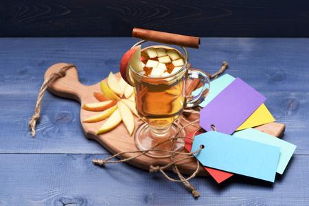 vin chaud: Un verre de délicieux glintwein ou vin chaud à la cannelle, des étiquettes colorées avec de la ficelle et de pomme en tranches sur une planche à découper sur fond bleu bois cru