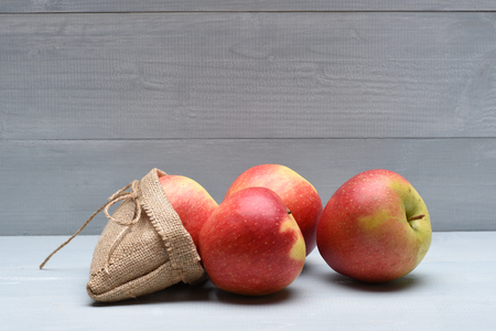 Fresh red apples with sack bag and string on vintage wooden background
