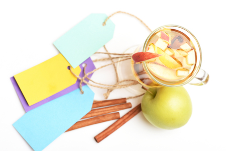 string top: Glass of delicious glintwein or mulled hot wine with natural fresh green apple and cinnamon, colorful tags with string isolated on white background, top view