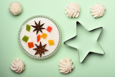 Marshmallows, white coconut candy, marmalade or jelly candies with anise in sugar and silver star on light green background Stock Photo