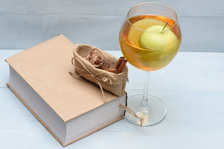 Glass of apple juice with natural fresh green apple placed inside, book and cinnamon inside sack bag with string on vintage wooden background Stock Photo