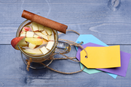 vin chaud: Un verre de délicieux glintwein ou vin chaud à la cannelle, des étiquettes colorées avec de la ficelle sur fond bleu bois vintage, vue de dessus