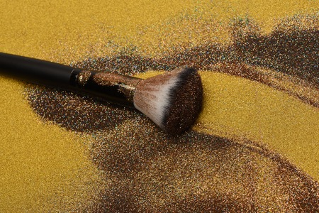 glister: Soft cosmetics brush on golden background, makeup concept