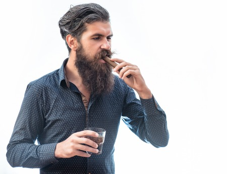 tough man: handsome bearded tough man with stylish hair mustache and long beard on serious face in blue fashion shirt want smoking cigar and holding glass of whiskey isolated on white, copy space