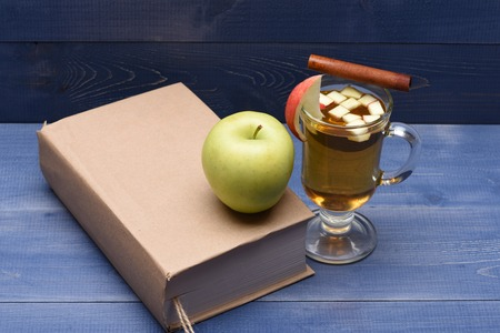 vin chaud: Glass of delicious glintwein or mulled hot wine with cinnamon and natural fresh green apple with book on blue vintage wooden background