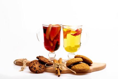 vin chaud: Deux verres de délicieux glintwein ou vin chaud chaud rouge et blanc sur une planche à découper avec fil, la cannelle, les noix et les biscuits à l'avoine isolé sur fond blanc