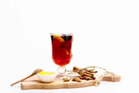 vin chaud: Glass of delicious glintwein or mulled hot wine on cutting board with thread, cinnamon, honey, wooden spoon and walnuts isolated on white background