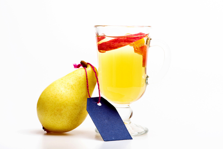 vin chaud: Glass of delicious glintwein or mulled hot wine, pear and blue tag isolated on white background