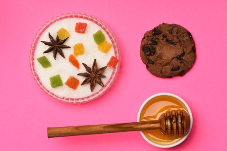Chocolate chip cookie with colorful marmalade or jelly candies, anise in sugar, honey with stick on pink background