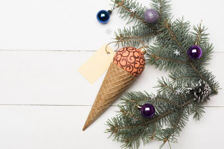 pinecones: Christmas baubles and decorations including ice cream cone, orange red christmas ball, yellow tag, christmas tree with brown pine cone and balls on vintage white background