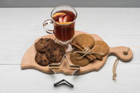 vin chaud: Un verre de délicieux glintwein ou vin chaud chaud sur une planche à découper avec de la cannelle, du fil, étoile d'argent et de biscuits à l'avoine sur fond de bois cru Banque d'images