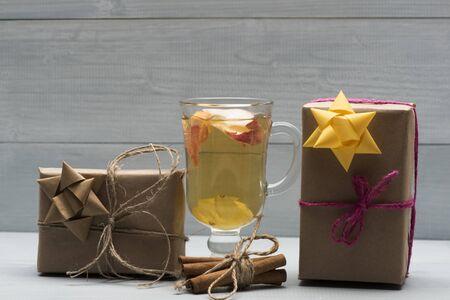 vin chaud: Un verre de délicieux glintwein ou chaud vin chaud, la cannelle, du fil et des cadeaux enveloppés dans du papier kraft avec un arc sur fond de bois cru