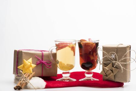 vin chaud: Two glasses of delicious glintwein or mulled red and white hot wine, cinnamon, gifts wrapped in craft paper with bow and snowflakes with Santa Claus red sock isolated on white background