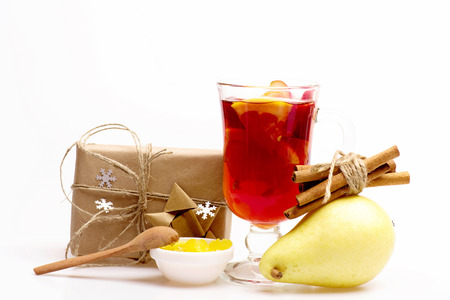 wine gift: Glass of delicious glintwein or mulled hot wine, gift wrapped in craft paper with bow with cinnamon, honey and pear isolated on white background