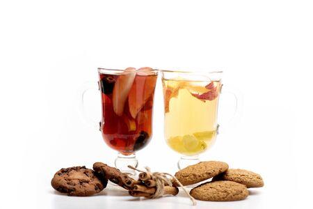 vin chaud: Deux verres de délicieux glintwein ou vin, la cannelle et biscuits à l'avoine chauds rouge et blanc chaud isolé sur fond blanc