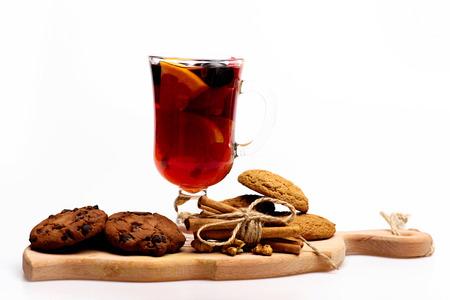 vin chaud: Un verre de délicieux glintwein ou vin chaud chaud sur une planche à découper avec fil, la cannelle, les noix et les biscuits à l'avoine isolé sur fond blanc, vue de côté