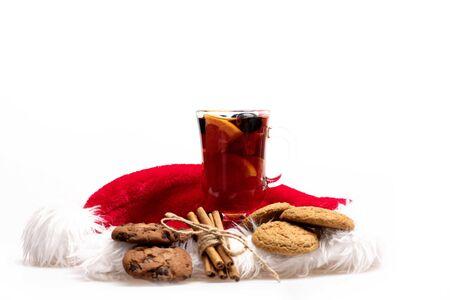 vin chaud: Un verre de délicieux glintwein ou de vin chaud, de cannelle et de flocons d'avoine chaud biscuits avec le Père Noël chapeau rouge isolé sur fond blanc, vue de côté Banque d'images