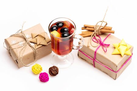 vin chaud: Glass of delicious glintwein or mulled hot wine, cinnamon, clews of yellow, brown, pink thread and gifts wrapped in craft paper with bow and snowflakes isolated on white background Banque d'images