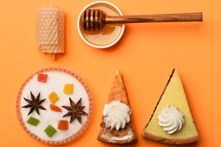 Set of slices of pie with poppy seeds, apple, marshmallows, honey and stick, colorful marmalade or jelly candies, anise and honeycomb on orange background