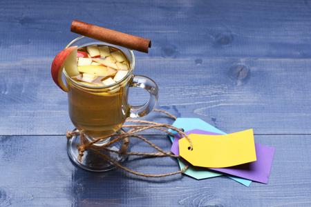 vin chaud: Un verre de délicieux glintwein ou vin chaud à la cannelle, des étiquettes colorées avec de la ficelle sur fond bleu bois cru
