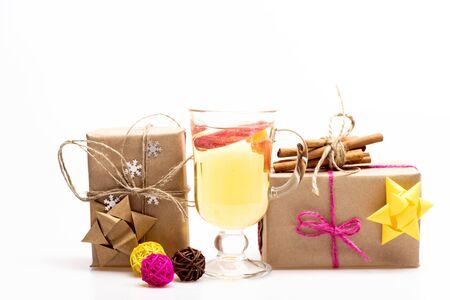 vin chaud: Un verre de délicieux glintwein ou vin chaud, cannelle, clews de jaune, brun, fil rose et cadeaux enveloppés dans du papier kraft avec un arc et des flocons de neige isolé sur fond blanc Banque d'images