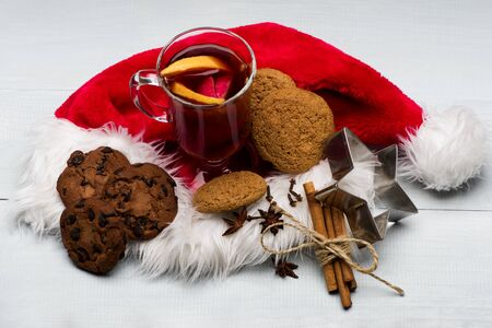 Glass of delicious glintwein or mulled hot wine, cinnamon, thread, anise, oatmeal cookies, silver star with Santa Claus red hat on vintage wooden background