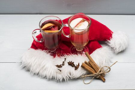 vin chaud: Two glasses of delicious glintwein or mulled red and white hot wine, cinnamon, thread, anise with Santa Claus red hat on vintage wooden background