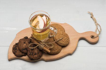 vin chaud: Un verre de délicieux glintwein ou vin chaud chaud sur une planche à découper à la cannelle, du fil et des biscuits à l'avoine sur fond de bois cru