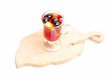 vin chaud: Un verre de délicieux glintwein ou vin chaud chaud sur une planche à découper avec un fil isolé sur fond blanc Banque d'images
