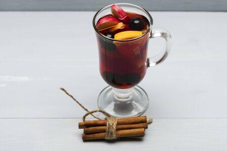 vin chaud: Un verre de délicieux glintwein ou vin chaud, de cannelle, de fil sur fond de bois cru Banque d'images