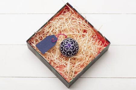 blue violet: Colorful Christmas or New Year decoration with Christmas box, violet silver christmas ball and blue tag with rose thread inside on vintage white background Stock Photo