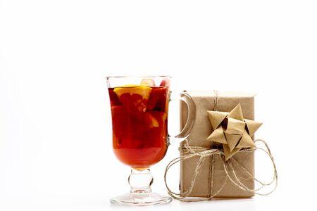 vin chaud: Un verre de délicieux glintwein ou vin chaud et cadeau enveloppé dans du papier kraft avec un arc isolé sur fond blanc