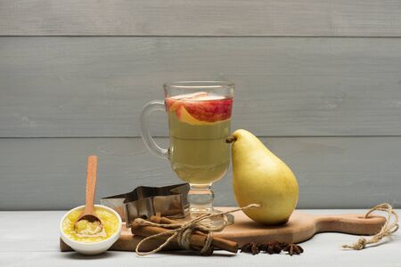 vin chaud: Glass of delicious glintwein or mulled hot wine on cutting board with cinnamon, thread, anise, pear, honey, wooden spoon and silver star on vintage wooden background