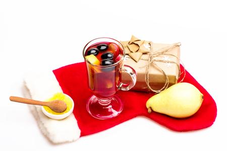 vin chaud: Un verre de délicieux glintwein ou chaud miel vin chaud, cuillère en bois, poire, cadeau enveloppé dans du papier kraft avec arc, flocons de neige et le Père Noël chaussette rouge isolé sur fond blanc