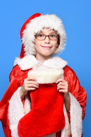 young cute santa claus boy with glasses in red sweater and new year hat holds decorative christmas or xmas stocking or boot on blue studio background
