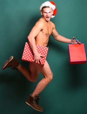 young handsome macho santa man with sexy muscular athletic strong body has bare torso and strong belly in christmas or xmas hat jumping with colorful present bag and box on green studio background Stock Photo