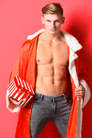 young handsome macho santa man with sexy muscular athletic strong body has bare torso and strong belly in new year sweater holding christmas or xmas present on red studio background Stock Photo