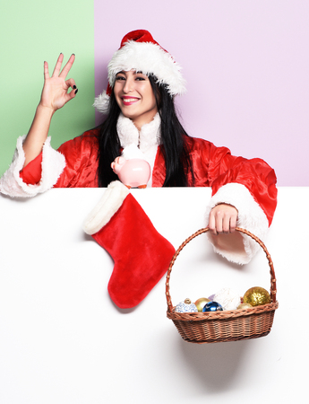 pretty cute sexy santa girl or smiling woman in red sweater and new year hat holds decorative christmas or xmas bucket with balls and stocking or boot showing ok on purple green studio background