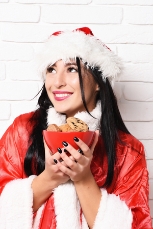 sexy sweater: pretty cute sexy santa girl or smiling happy brunette woman in new year sweater and hat holds christmas or xmas chocolate ?hip cookies in bowl on white brick wall background Stock Photo