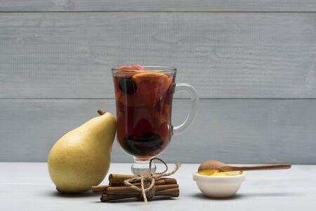 vin chaud: Un verre de délicieux glintwein ou vin chaud, de cannelle, de fil, de poire, de miel, une cuillère en bois sur fond de bois cru