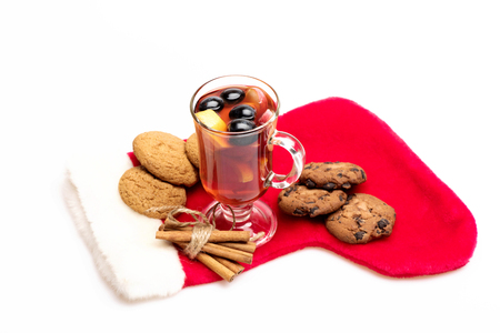 vin chaud: Glass of delicious glintwein or mulled hot wine, cinnamon and oatmeal cookies with Santa Claus red sock isolated on white background
