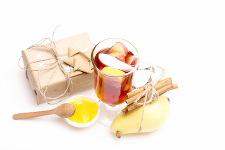 wine gift: Glass of delicious glintwein or mulled hot wine, gift wrapped in craft paper with bow, snowflakes and cinnamon, honey, pear isolated on white background