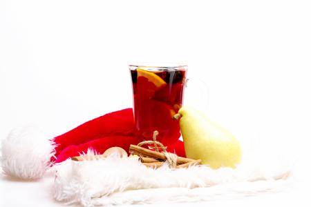 vin chaud: Un verre de délicieux glintwein ou vin chaud, cannelle, poire, cuillère en bois et le Père Noël chapeau rouge isolé sur fond blanc