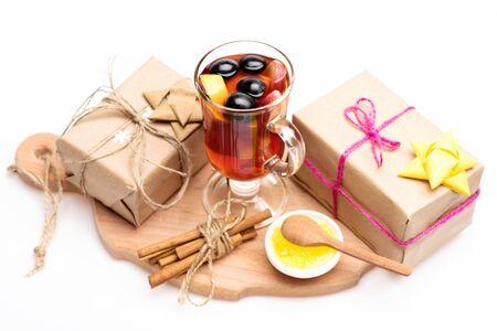 vin chaud: Un verre de délicieux glintwein ou vin chaud chaud sur une planche à découper avec un fil, la cannelle, le miel, une cuillère en bois et cadeaux emballés dans du papier kraft avec un arc et des flocons de neige isolé sur fond blanc